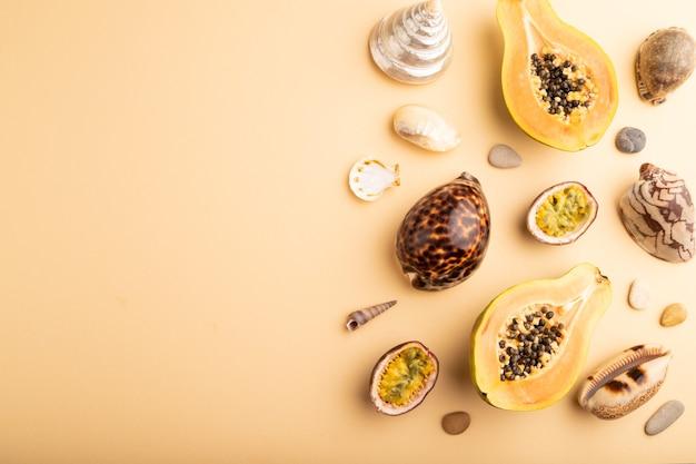 Papaye coupée mûre, fruit de la passion, coquillages, cailloux sur fond pastel orange. vue de dessus, mise à plat,