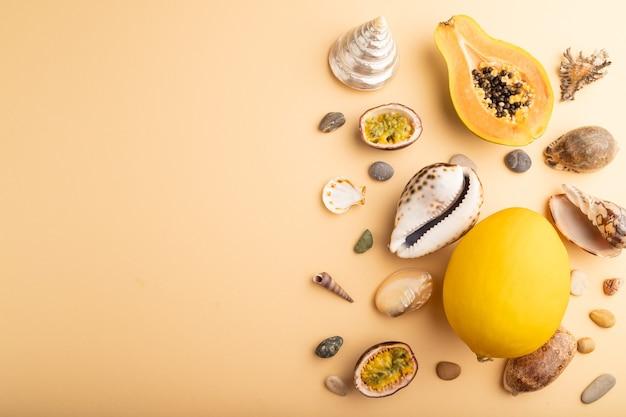 Papaye coupée mûre, fruit de la passion, melon, coquillages, cailloux sur fond pastel orange. vue de dessus,