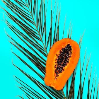 Papaye sur fond bleu. art végétalien minimal à plat