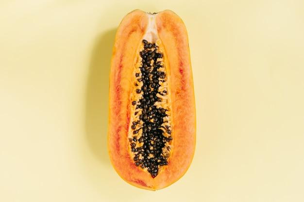 Papaye sur fond jaune pastel, concept de cuisine créative, fruits tropicaux. mise à plat. vue de dessus. voyage tropical, fruits exotiques. concept végétalien et végétarien. photo de haute qualité