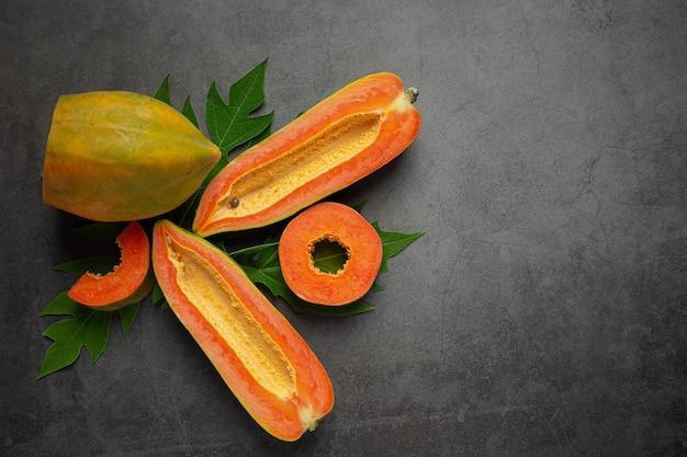 Papaye fraîche, coupée en deux, posée sur un sol sombre