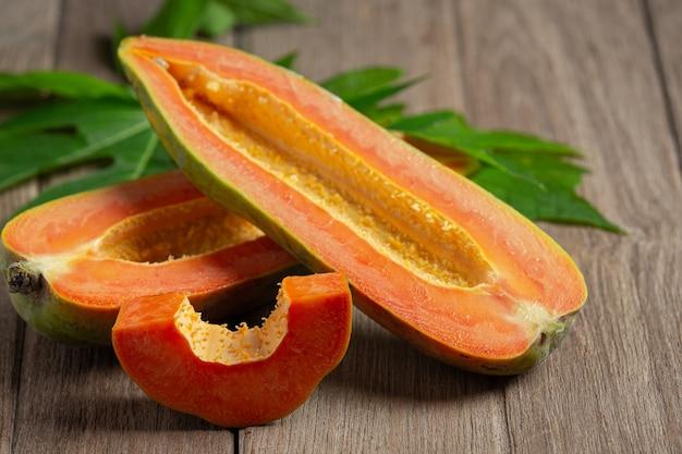 Papaye fraîche, coupée en morceaux, posée sur un plancher en bois