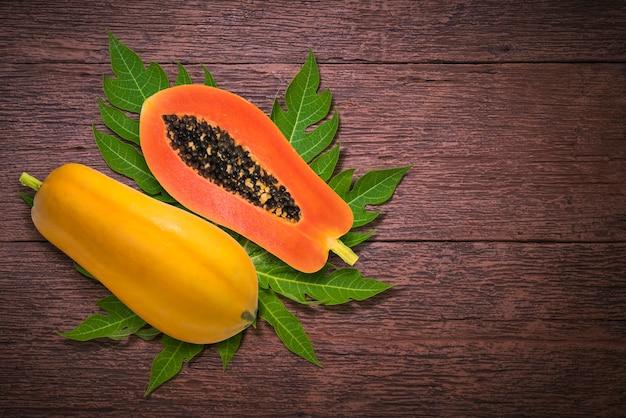Papaye sucrée sur le plat avec feuille de papaye verte sur fond de bois.