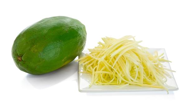 Papaye verte rappée pour faire une salade sur fond blanc