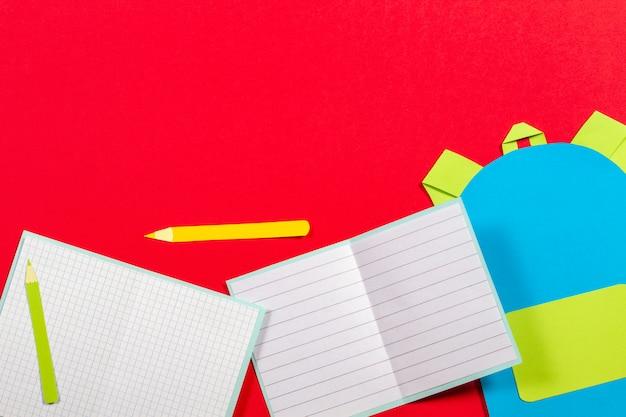 Papercut de l'éducation scolaire. sac à dos cartable, livres cahiers fournitures scolaires papier découpé