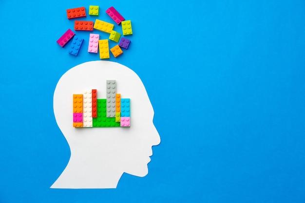 Papercut silhouette de tête humaine avec des pièces de constructeur colorées
