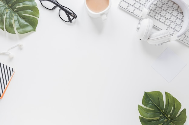 Papeterie et appareils sur un bureau blanc orné de feuilles