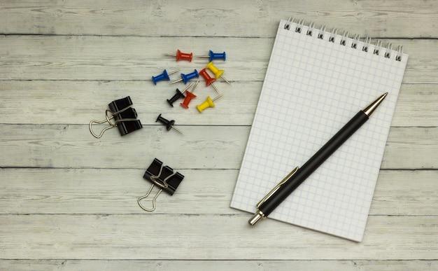 Papeterie: bloc-notes vierge, stylos, boutons, sur un bureau en bois gris. vue de dessus. espace de copie.