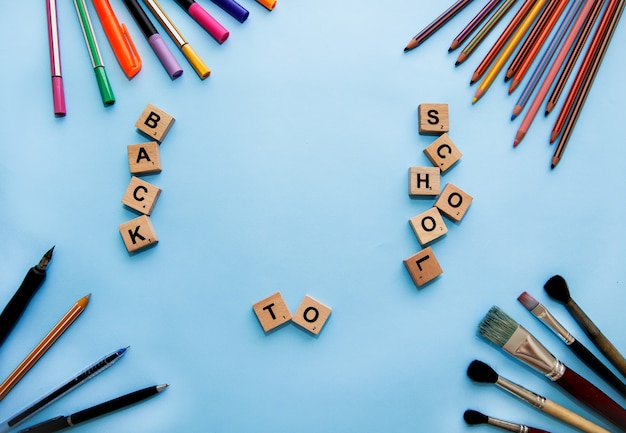 Papeterie sur le bureau. retour au concept d'école. cadre de fournitures scolaires. papeterie et lettres sur la table.