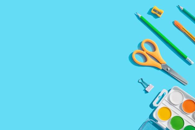 Papeterie: ciseaux, stylos, crayons, trombones, aquarelles. le concept d'apprentissage, la créativité des enfants. fond bleu, vue de dessus, mise à plat, espace de copie.