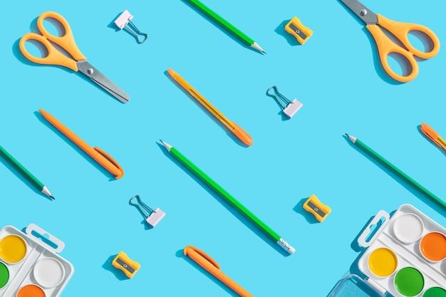 Papeterie: ciseaux, stylos, crayons, trombones, aquarelles. le concept d'apprentissage, la créativité des enfants. fond bleu, vue de dessus, pose à plat.