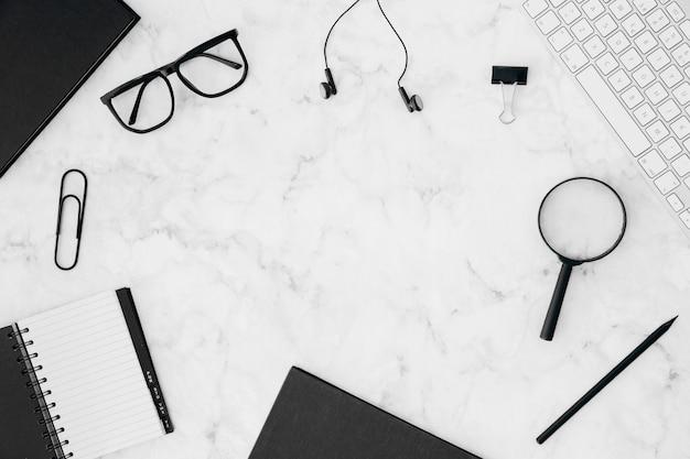 Papeterie; clavier et lunettes de vue sur fond texturé en marbre blanc
