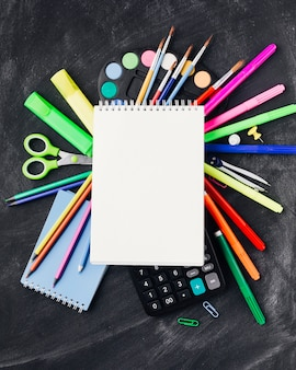 Papeterie colorée, peintures, calculatrice sous un cahier sur fond gris