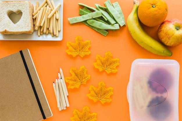 Papeterie et feuilles près d'aliments sains