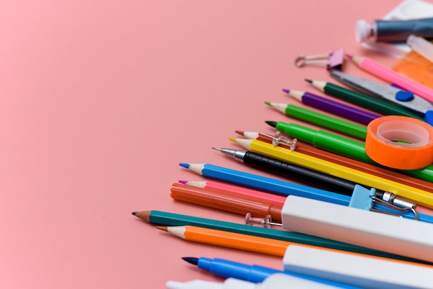 Papeterie de fournitures scolaires sur fond rose. vue d'en-haut.