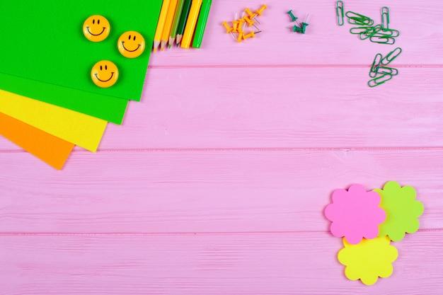 Papeterie jaune et vert et ressenti sur fond en bois rose.