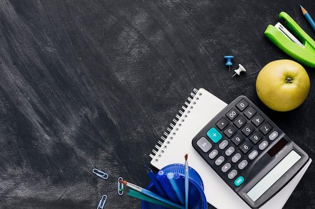 Papeterie avec pomme et calculatrice sur tableau noir