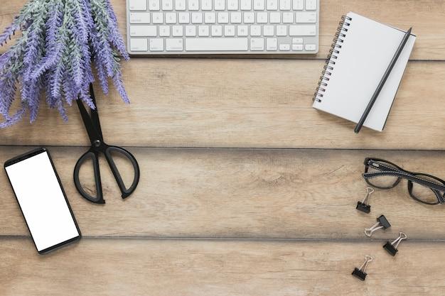 Papeterie à proximité d'appareils électroniques et de fleurs de lavande sur le bureau