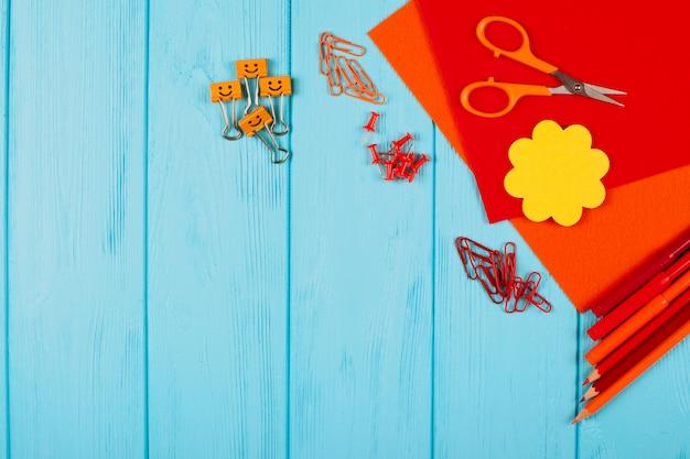 Papeterie rouge et orange sur un fond en bois bleu.