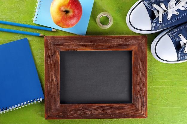Papeterie scolaire et petit tableau sur fond vert, vue de dessus