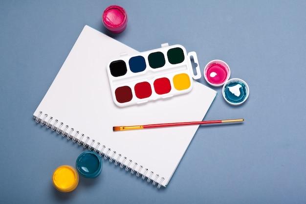 Papier, aquarelles, pinceau et quelques trucs d'art bouchent la vue de dessus