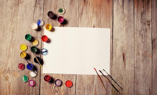 Papier, aquarelles, pinceau et quelques trucs d'art sur table en bois