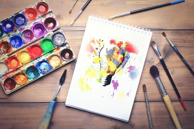 Papier, aquarelles et pinceau sur table en bois