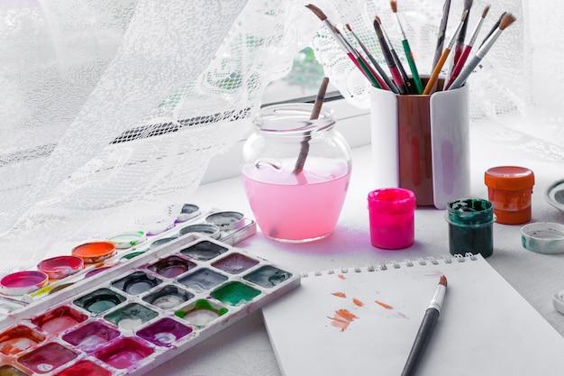 Papier, aquarelles, pinceaux et objets d'art sur une table en bois