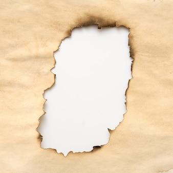 Papier beige froissé vieilli avec trou brûlé sur blanc. conception abstraite grunge