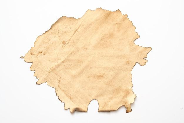 Papier beige vieilli avec bord brûlé sur blanc. conception abstraite grunge