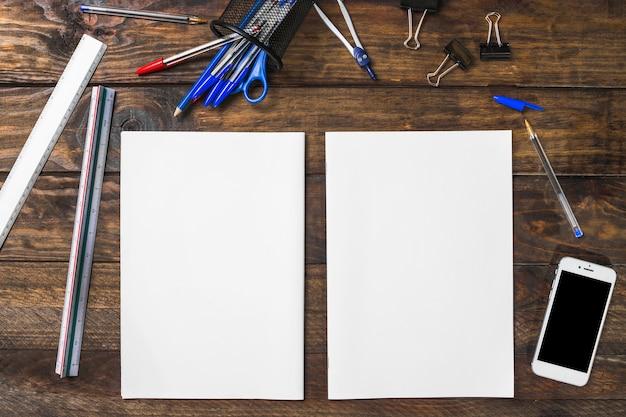 Papier blanc blanc entouré de papeterie et smartphone sur table en bois