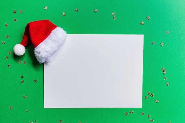 Papier blanc avec bonnet de noel et confettis