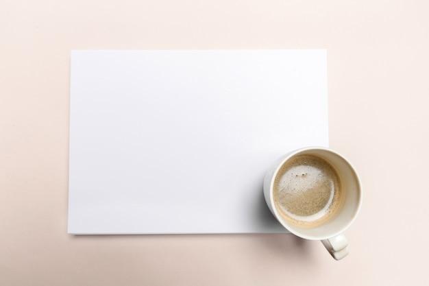 Papier blanc sur le bureau pastel rose