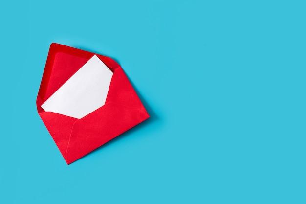 Papier blanc avec copie espace dans une enveloppe rouge sur fond bleu