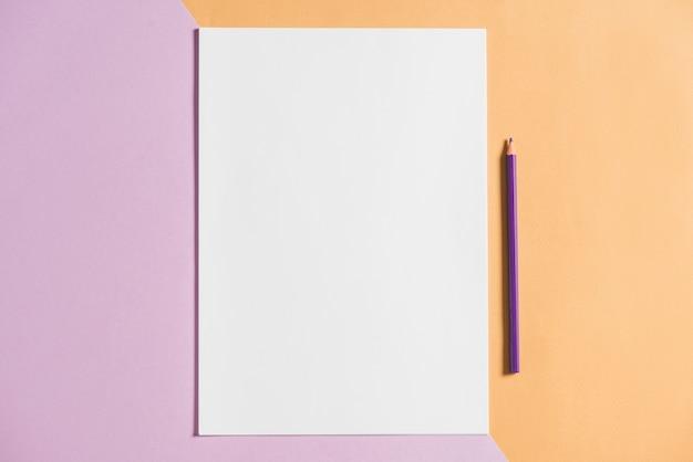 Papier blanc avec un crayon sur fond coloré