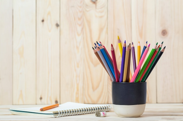 Papier blanc et crayons colorés sur la table en bois