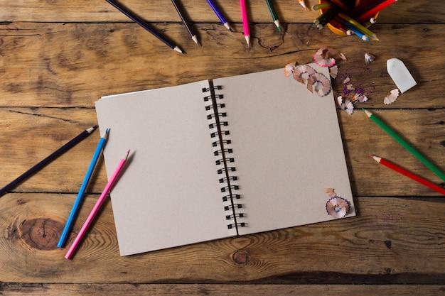 Papier blanc et crayons colorés sur une vieille table en bois. mise à plat, vue de dessus