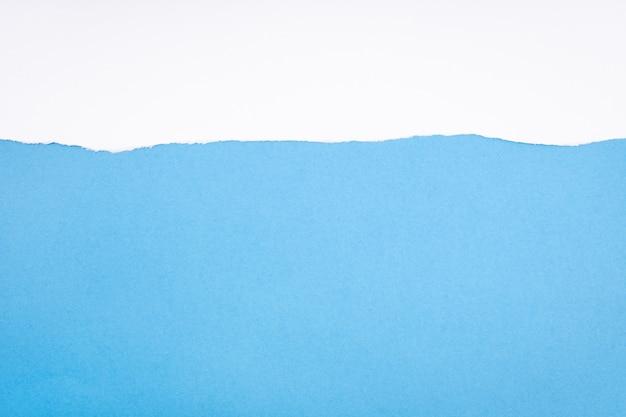 Papier blanc déchiré sur carton bleu