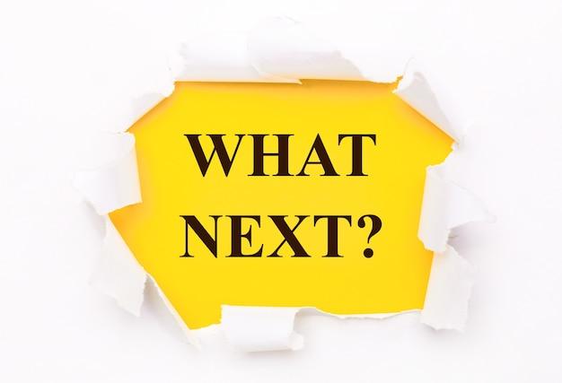 Le papier blanc déchiré se trouve sur un fond jaune vif avec le texte what next