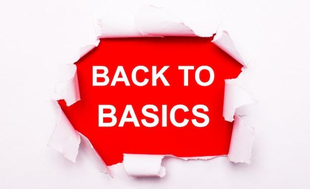 Le papier blanc déchiré se trouve sur un fond rouge. sur le rouge, le texte est blanc retour aux bases.