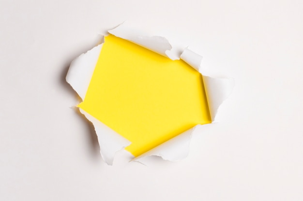 Papier blanc déchiré en surface, sous papier de couleur