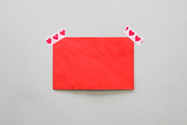 Papier blanc fixé avec du ruban adhésif avec des coeurs