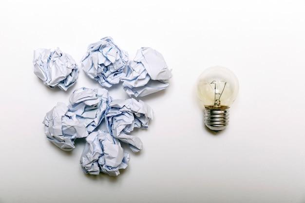 Papier blanc froissé et métaphore de l'ampoule pour une bonne idée