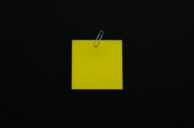 Papier blanc jaune avec trombone sur fond sombre. concept de mise à plat noir minimaliste.