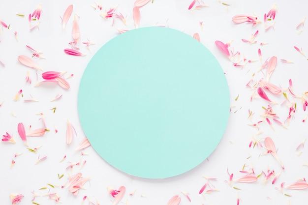 Papier blanc avec des pétales de fleurs sur la table