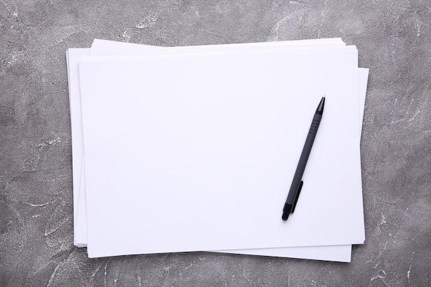 Papier blanc pile avec un stylo sur béton gris
