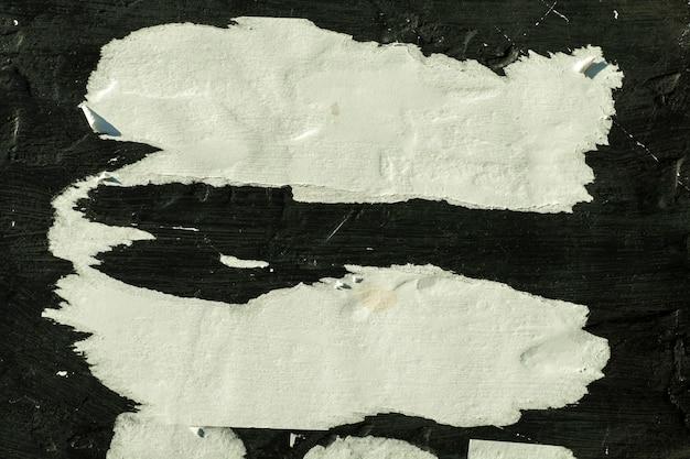 Papier blanc avec des plis sur le mur noir.