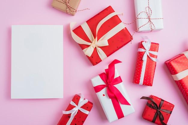 Papier blanc près de divers cadeaux de la saint-valentin