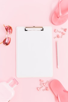 Papier blanc sur le presse-papiers entouré d'un sac de bagage miniature; des lunettes de soleil; trombones; crayon et tongs sur fond rose