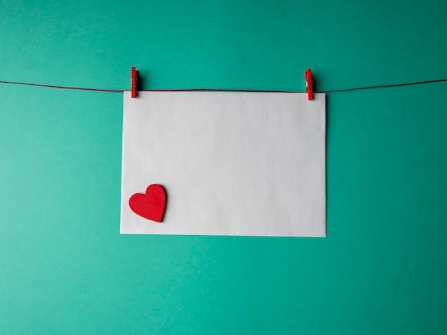 Papier blanc qui pèse sur une corde rouge et est fixé avec deux pinces à linge et a un cœur rouge dessus sur un fond vert. un modèle pour votre projet pour la saint-valentin